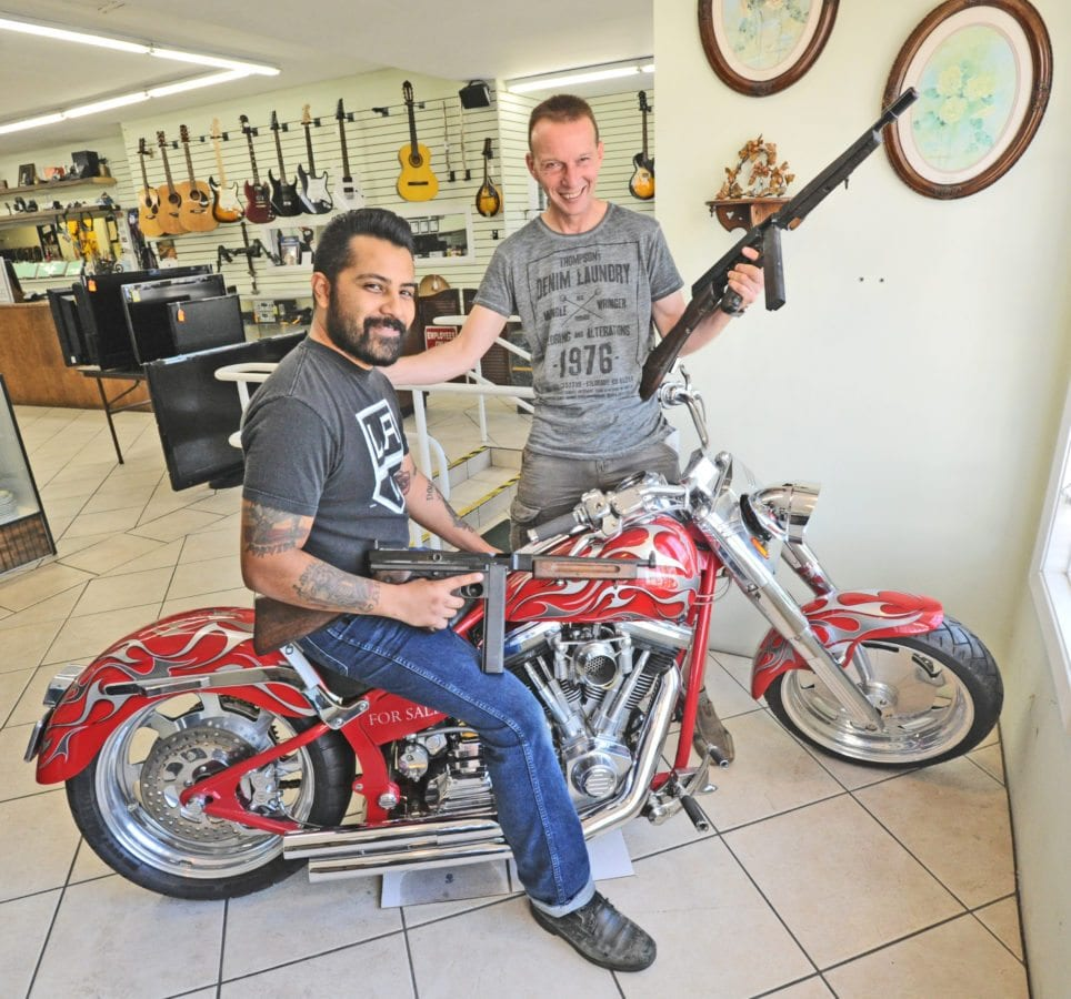 Abe's Pawn Shop Manger Mike Ray, left, and Owner Thomas Bayer sit on a Merch(cq) Custom Chopper/Cruiser motorcycle in the window as they display two movie prop, non-firing sub-machine guns at Abe's on Tuesday. Dan Watson/The Signal