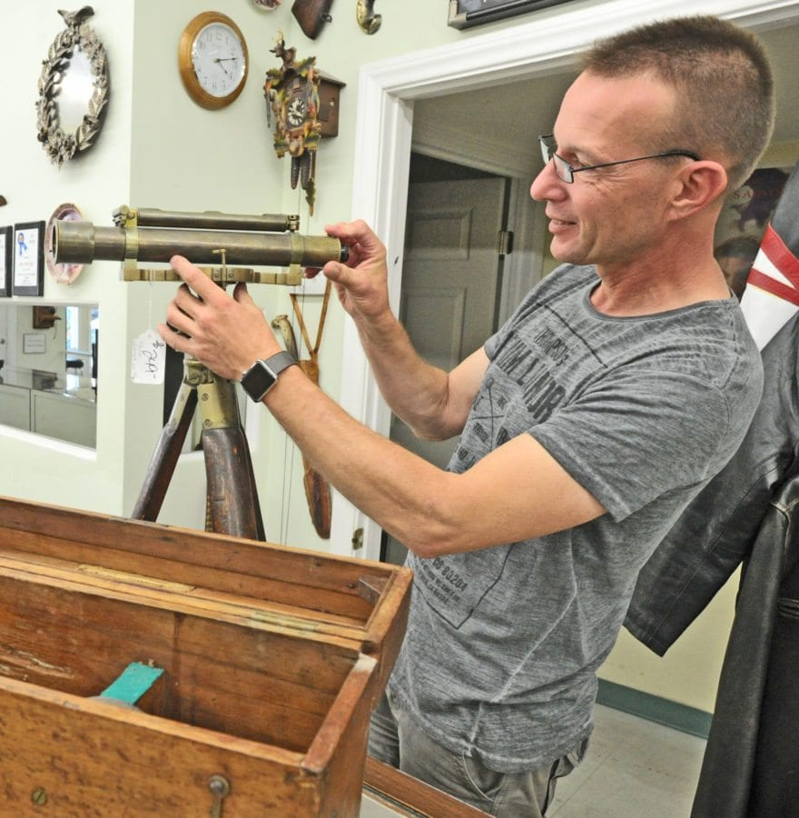 Abe's Pawn Shop owner Thomas Bayer assembles a brass surveyor's transit with tripod and original case made by Young and Sons of Philadelphia. The company made engineering, mining and surveying equipment from 1820 until 1918. Dan Watson/The Signal