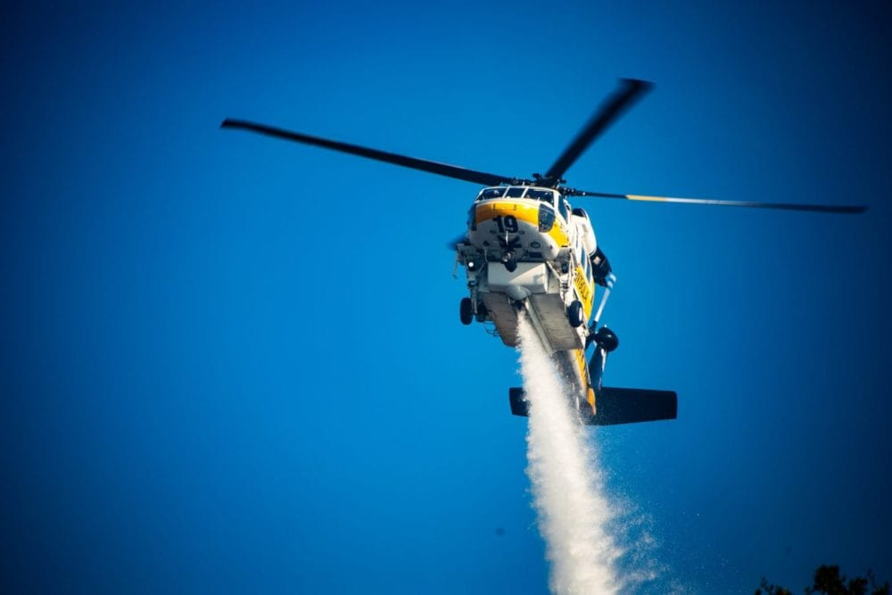 Los Angeles County Fire Copter 19 makes a water drop on the South Fire in Newhall. Cory Rubin/ The Signal