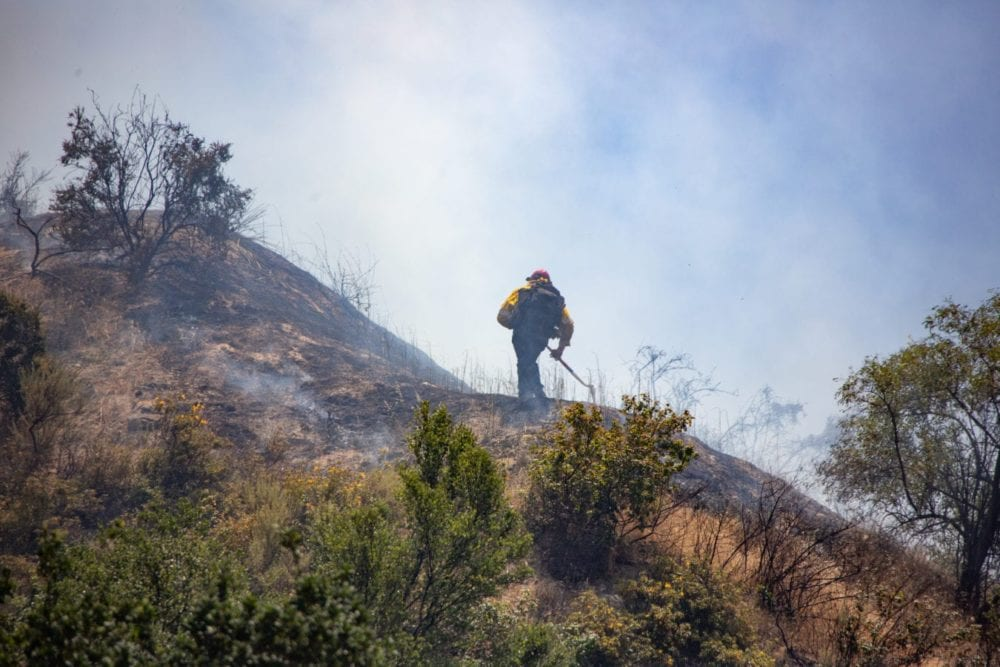 A lone LA County Fire Camp Superintendant walks a scorched peak during the SIerra Fire on Tuesday, June 19 2018.  Cory Rubin/ The Signal