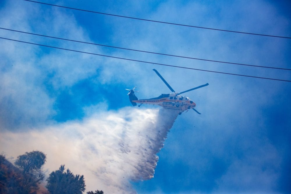 Los Angeles County Fire Copter 15 makes a drop in the Sierra Fire on Tuesday, June 19th 2018.  Cory Rubin/ The Signal