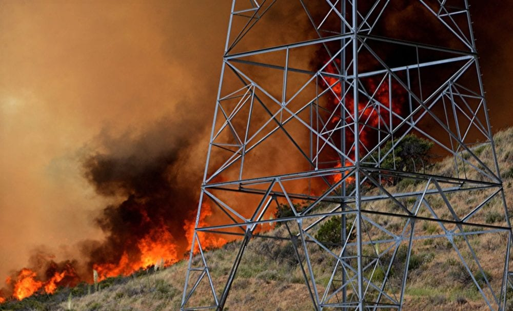Flames of the Stone Incident Fire sweep along a hill near power lines. photo for The Signal by Rick McClure.