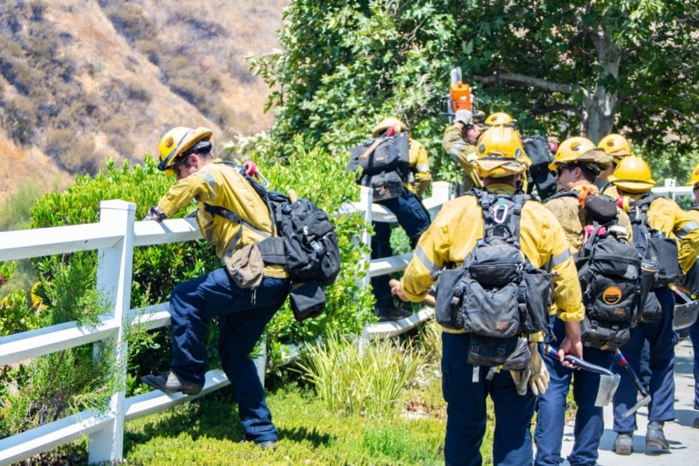 Camp crews make gain acces to the Tesoro Fire in North Valencia by hopping a fence.  The Fire started at 10:48 am and the cause is under investigation.  Cory Rubin/ The Signal