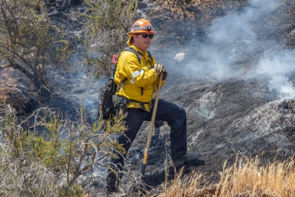 A Los Angeles County Firefighter keeps a lookout for flames at the Tesoro Fire in North Valencia.  The Fire started at 10:48 am and the caue is under investigation.  Cory Rubin/ The Signal