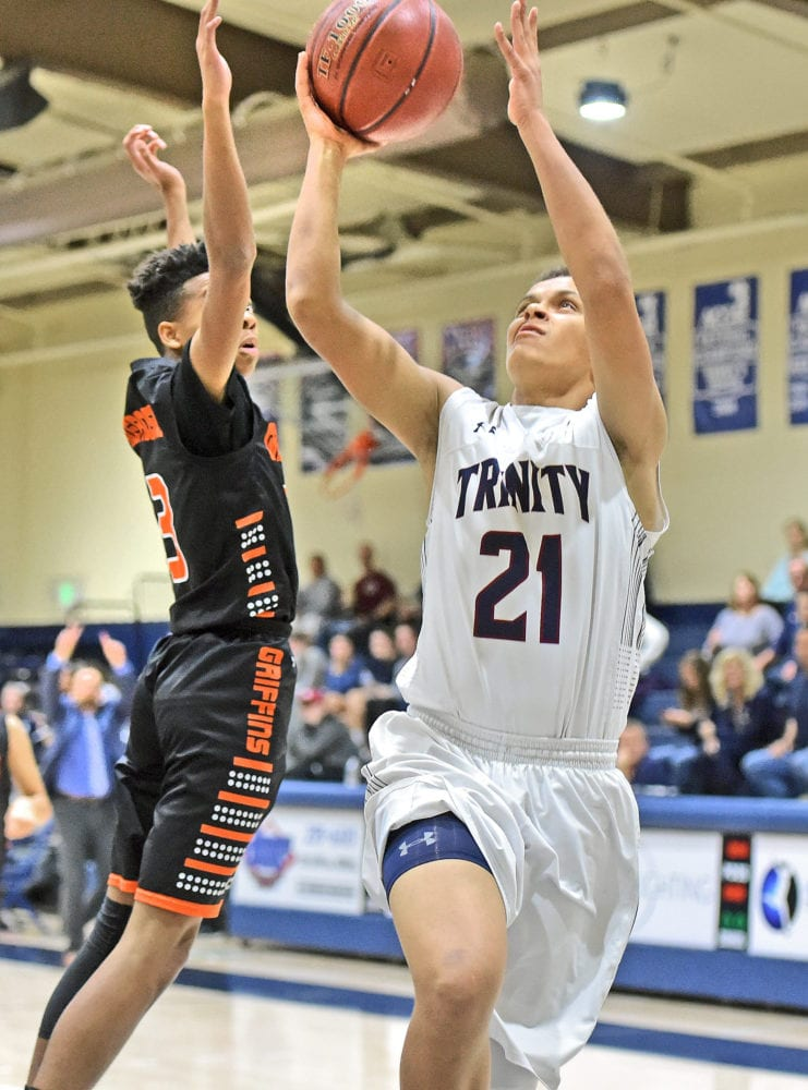 Trinity Classical Academy's Kyle Fields (21) shoots over Palmdale Aerospace Academy defender Isaiah Enyard (3) at The Master's University on Tuesday. Dan Watson/The Signal