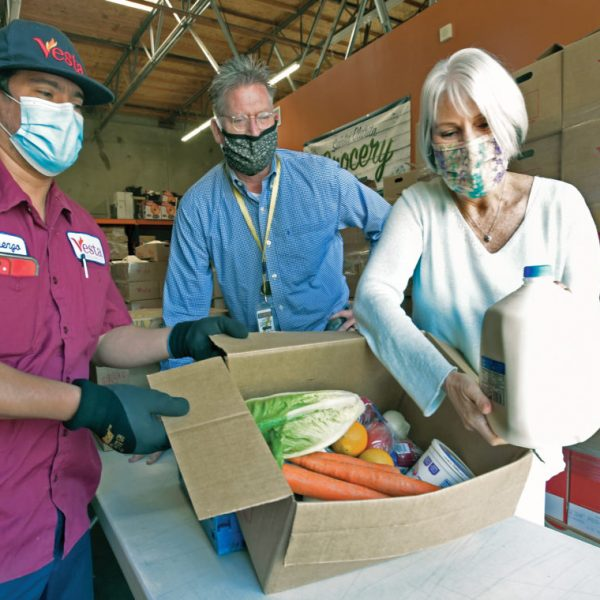 SIGNAL FILE PHOTO: From left, Vesta driver,  Lorenzo Cisneros, Santa Clarita Grocery Founder and Executive Director, Bradley Grose and Child & Family Center CEO Joan Aschoff examine the contents of one of the 250 boxes of food delivered at Santa Clarita Grocery in Santa Clarita on Friday, May 29, 20.  Dan Watson/The Signal