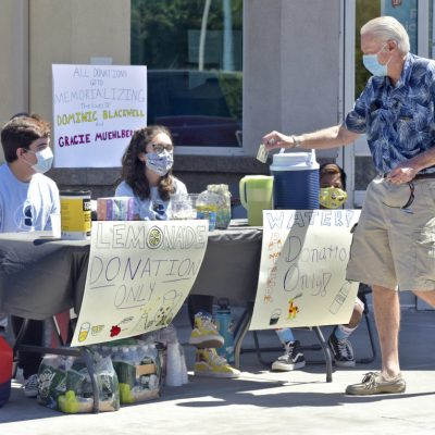 Derek Diaz, 16, left, and Mia Tretta, 15, thank Santa Clarita resident Larry Johnson, right, as he drops a donation in a mason jar during a lemonade stand fundraiser to memorialize Dominic Blackwell and Gracie Muehlberger which was held at the Walgreens Drug Store in Santa Clarita on Saturday, July 18, 2020.  Dan Watson/The Signal