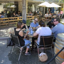 Dinners sit behind K-rails as they eat in the street outside Smokehouse on Main, as on Main Street in Newhall is close to increase outside seating for restaurants on Saturday, July 18, 2020.  Dan Watson/The Signal