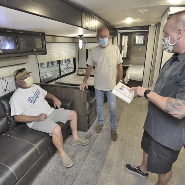 Customers Gary Morgan, left, Rich Kariger from Lancaster discuss the better insulation available on a Wilderness by Heartland travel trailer with sales manager Jordan Heck at All Valley RV Center in Acton. PHOTO BY DAN WATSON / THE SIGNAL