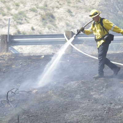 Los Angeles County Fire Department personnel mop up a small vegetation fire near the Interstate 5 and Highway 14 intersection on Thursday, July 23, 2020. Dan Watson/The Signal