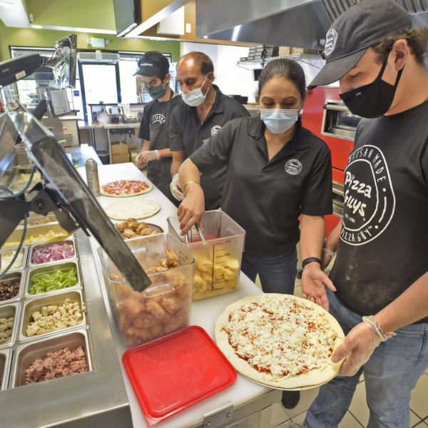 From Left, server, Dylan Santa Cruz, Lucky and Manjit Singh and server, Seth Garden at Pizza Guys.  080120.  Dan Watson/The Signal