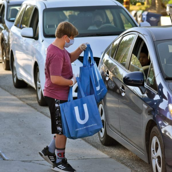 Zach Marshall, 13, hands out bags to some of the hundreds of waiting cars during the Peace Bag Giveaway, held in front of Santa Clarita Valley Boys & Girls Club in Newhall on Thursday, August 06, 2020.  Dan Watson/The Signal