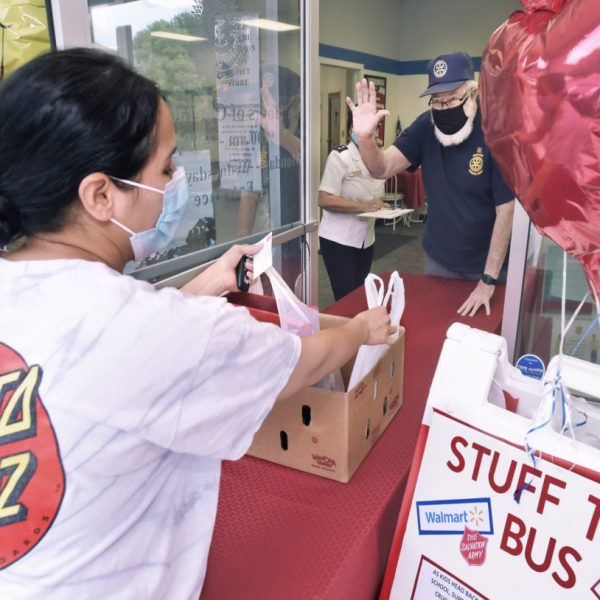 Rotary Club of Santa Clarita Sunrise volunteer Richard Cook gives Jessica Guerrero bags of age appropriate school supplies for her children during the