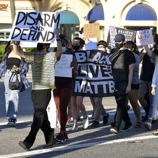 Black Live Matter demonstrators cross Valencia Boulevard during a protest held on the corner of Magic Mountain Parkway and Valencia Boulevard on Friday, August 14, 2020.  Dan Watson/The Signal