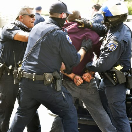 A man struggles with officers as he is detained after he was involved in a fight with a California Highway Patrol  Officer at the Mobil gas station on the corner of The Old Road and Sloan Canyon Road in Castaic on Friday, August 21, 2020.  Dan Watson/The Signal