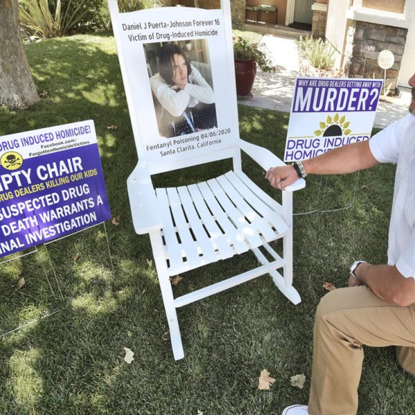 Jaime Puerta kneels next to the display he set up on his lawn in Santa Clarita on Saturday for his son Daniel J. Puerta-Johnson who died of fentanyl poisoning in April 2020,   082920  Dan Watson/The Signal
