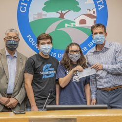 Saugus High School students Derek Diaz and Mia Tretta present Santa Clarita Mayor Cameron Smyth, right, and Mayor Pro Tem Bill Miranda with a check after over $6,000 for a memorial for the victims of the Saugus Shooting with a lemonade stand. September 03, 2020. Bobby Block / The Signal.