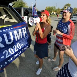 Cindy Josten, center, uses a megaphone to rally the drivers as they prepare to start the Trump/ Recall Newsom parade in Valencia on Saturday, 092620.  Dan Watson/The Signal