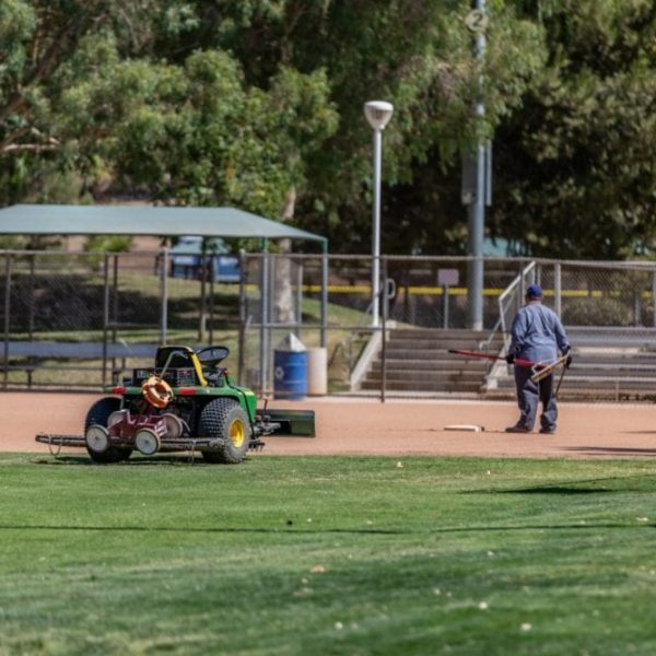 A city worker works on ball field at Central Park as a part of improvements made to several city parks.  Cory Rubin/The Signal