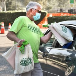 Arts and Events Supervisor Patrick Downing hands out bags of supplies to one of the 900 registered participants during the 2020 Neighborhood Cleanup and Online Environmental Expo at Central Park in Saugus on Saturday, September 26, 2020.  Dan Watson/The Signal