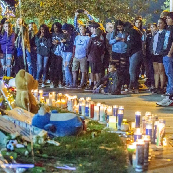 Residents stand around the memorial set up at the Central Park flag pole at the Saugus Strong Vigil Sunday night.  Cory Rubin/The Signal