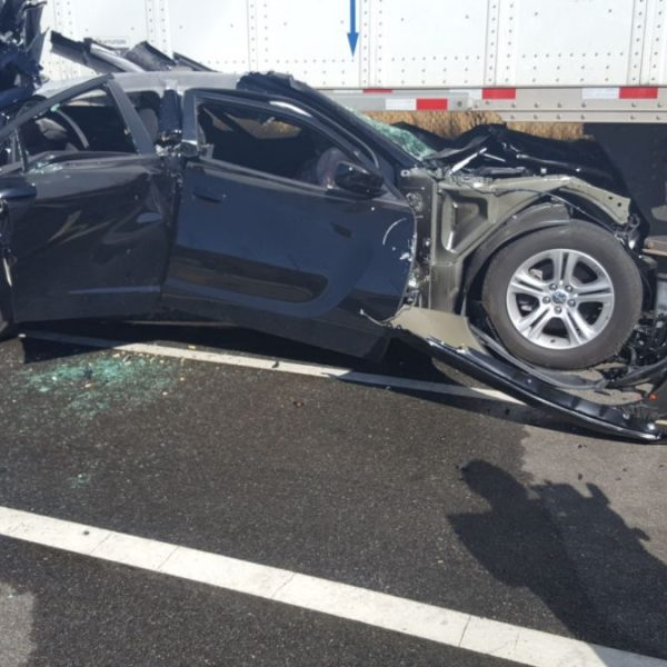 Firefighters examine a black Dodge Charger that crashed into a semi-truck trailer Friday morning. Dan Watson / The Signal.