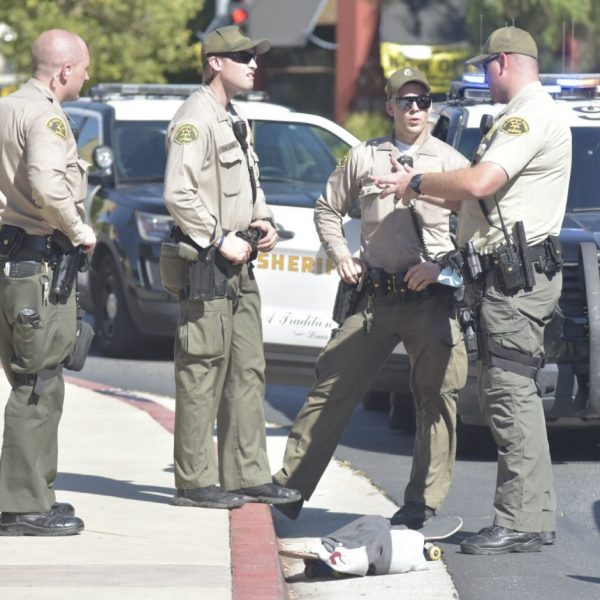 Deputy, right, describes his scuffle with suspect on Town Center Drive near McBean skateboard is at his feet. Dan Watson / The Signal.