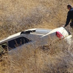 A CHP officer examines a white sedan that went about a hundred yards down in the bank went off the southbound 5 Freeway just north of Lake Hughes Road in Castaic. Dan Watson / The Signal.
